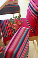 In a country dining room chairs upholstered in a shocking pink stripe stand out against a stone-flagged floor