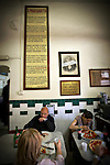 Photo of people eating pizza at the Antica Pizzeria de Michele in Naples, Italy.