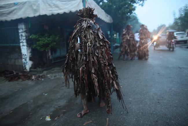 """Participants in the annual Taong Putik, or """"mud people,"""" festival walk through the streets, asking alms from passersby, while on their way to a special Mass at the Catholic church in the village of Bibiclat, on Luzon island, Philippines. The festival honors St. John the Baptist, and the mud, banana leaves and vines that devotees wear symbolize the animal skins the saint wore in the Bible. June 24, 2011."""