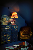 A brown velour armchair stands in the corner of a room next to a cupboard with a distressed paint finish. A table lamp with a red floral shade illuminates the dark blue room.