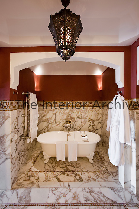 The en-suite bathroom with marble floor and a free standing bath