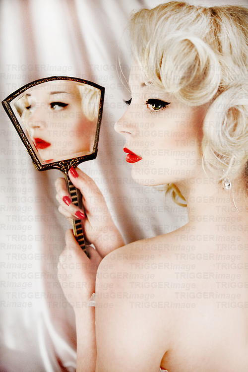 Delicate blonde girl looking into mirror with her back to the viewer