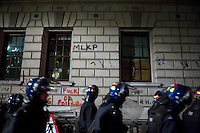 Riot police walk past smashed windows and graffiti on the Treasury building during a student demonstration in Westminster, central London on the day the government passed a bill to increase university tuition fees. .