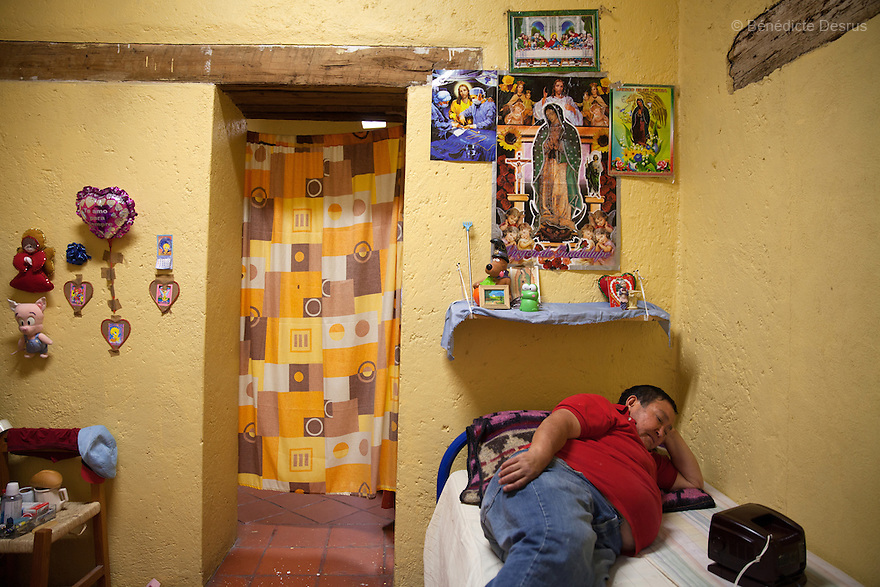Patricia, a resident of Casa Xochiquetzal, watches television in her bedroom at the shelter in Mexico City, Mexico on September 2, 2013. Casa Xochiquetzal is a shelter for elderly sex workers in Mexico City. It gives the women refuge, food, health services, a space to learn about their human rights and courses to help them rediscover their self-confidence and deal with traumatic aspects of their lives. Casa Xochiquetzal provides a space to age with dignity for a group of vulnerable women who are often invisible to society at large. It is the only such shelter existing in Latin America. Photo by Bénédicte Desrus