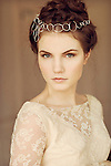 Portrait of young woman with sterling silver headpiece and white lace dress looking straight forward