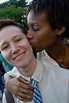 Head and shoulders portrait of two lesbians in Washington Square Park after the end of the Dyke March down 5th Avenue. African American wear bindi to honor third eye. Caucasian is wearing a tie.