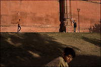 playing cricket along the walls of the badshahi mosque in the old city of lahore