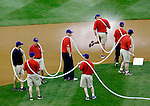 TEAM WORK -- How many grounds crew members does it take to hold up the hose as the field is prepped for Friday nights Iowa Cubs New Orlean Zephyrs game?  Apparently, 8. The game was held at Principal Park in Des Moines, Iowa.
