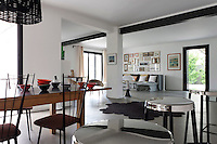 The wooden dining table in the open plan living area has been covered with a layer of waxed steel coated with matt varnish