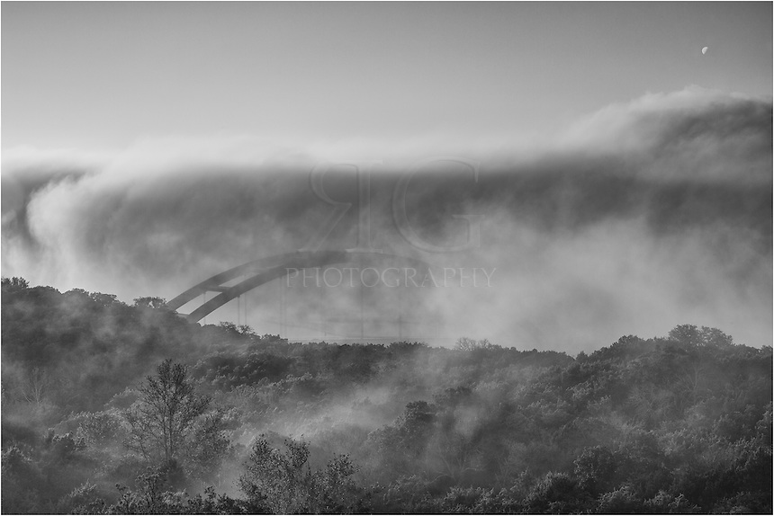 The first signs of Pennybacker Bridge begin to show up as fog recedes from the Colorado River basin on a cold December morning. The Austin sky line, usually visible in the distance from this vantage point above the iconic Austin bridge, is nowhere to be seen in this black and white image.