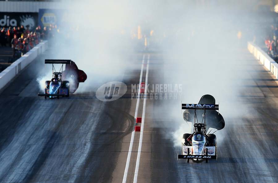 Feb. 22, 2013; Chandler, AZ, USA; NHRA top fuel dragster driver Brandon Bernstein (right) blows up alongside Mike Strasburg during qualifying for the Arizona Nationals at Firebird International Raceway. Mandatory Credit: Mark J. Rebilas-