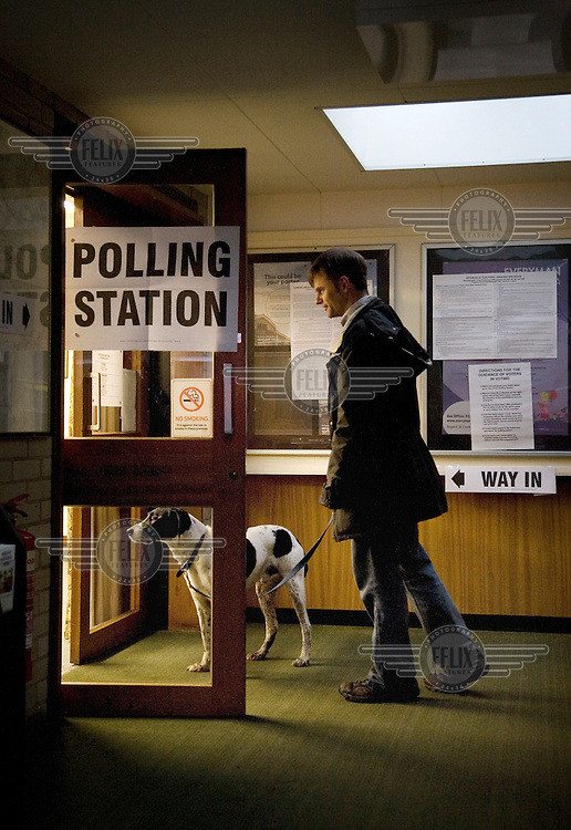 A man and his dog arrive at the Mortimer Rooms polling station during the Nailsworth Parish council elections in Gloucestershire.