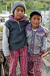 Two Guatemalan boys in traditional clothes pose outside their house in a village near Totos Santos Cuchumatan, Western Highlands, Guatemala