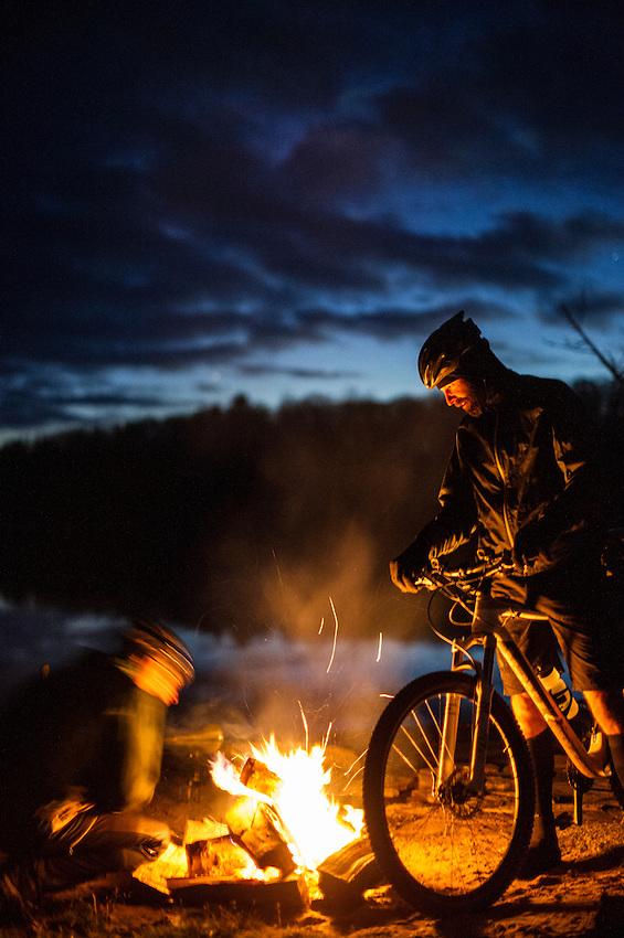 A mountain biker lights a campfire during a night ride.