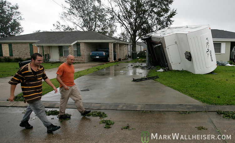 Adrian (R) and his son John Herbert walk past an overturned travel trailer in their neighborhood in Houma, Louisiana which was heavily damaged as Hurricane Gustav passes through September 1, 2008.    (Mark Wallheiser/TallahasseeStock.com)
