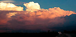 Cumulous thunderhead clouds before storm at sunset with auto headlights