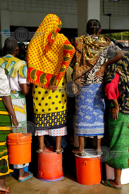 Women standing on their buckets during an auction at the city's Magogoni fish market. The women - small-scale enterpreneurs - will then prepare the fish and sell it on the city's streets.