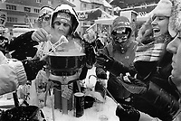Switzerland. Canton Bern. Wengen. A group of friends from the Gruyère area (Fribourg) eat a traditional cheese fondue outside during the FIS Ski World Cup Lauberhorn. Fondue is a Swiss dish of melted cheese served in a communal pot (caquelon or fondue pot) over a portable stove (réchaud) heated with a candle or spirit lamp, and eaten by dipping bread into the cheese using long-stemmed forks. It was promoted as a Swiss national dish by the Swiss Cheese Union (Schweizerische Käseunion) in the 1930. Wengen is a mountain village in the Bernese Oberland of central Switzerland. Located in the canton of Bern at an elevation of 1,274 m (4,180 ft) above sea level, it is part of the Jungfrauregion. 14.01.17 © 2017 Didier Ruef