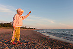 Young Kid Girl Throwing Stone into Water on Beach