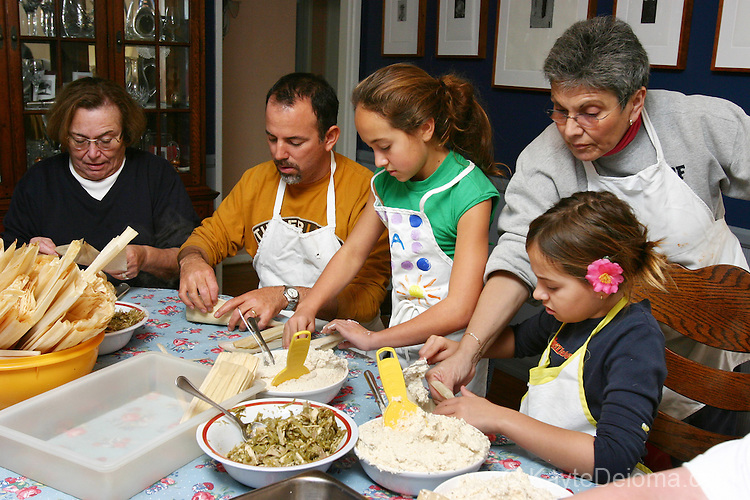 Grandmother helps granddaughter with the proper way to fold a tamal as other family members work at the table at a family Tamalada (tamale making party), Torrance, CA