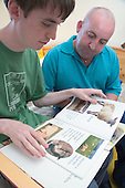 Teenage boy with Autism learning to read with help of his carer.  MR