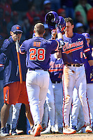 Left fielder Seth Beer (28) of the Clemson Tigers is congratulated after homering in the first inning of the Reedy River Rivalry game against the South Carolina Gamecocks on Saturday, March 4, 2017, at Fluor Field at the West End in Greenville, South Carolina. Clemson won, 8-7. (Tom Priddy/Four Seam Images)