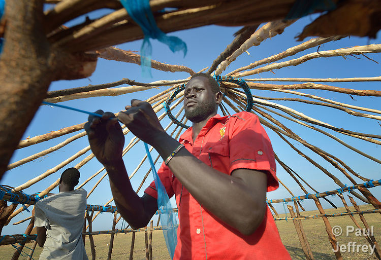Dau Chol Thuc works on the roof of his new house in Dong Boma, a Dinka village in South Sudan's Jonglei State, on April 12, 2017. Most of the villagers recently returned home after being displaced by rebel soldiers in December, 2013, and they face serious challenges in rebuilding their village.<br /> <br /> The blue fabric used to fasten many of the sticks together is torn from insecticide-treated bednets, which villagers have discovered provide a termite-resistant material for construction.<br /> <br /> The Lutheran World Federation, a member of the ACT Alliance, is helping villagers restart their lives with support for housing, livelihood, and food security.