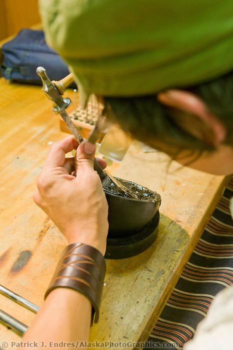 Native artist Nicholas Galanin works on metal bracelets at the Sitka National Historic Park in the coastal town of Sitka, Alaska