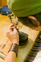 Native artist Nicholas Galanin works on metal bracelets at the Sitka National Historic Park in the coastal town of Sitka, Alaska
