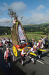 Uppermill, Saddleworth, Yorkshire, UK. The Saddlewoth Rushcart is pulled up to St Chad's Church, Saddleworth for the Rushbearing church service. The 'Jockey',  riding in top of the Rushcart is John Squirrel.