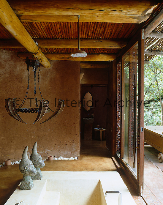 This bathroom has a sunken bath and a copper-wire chandelier and opens through sliding glass doors onto a terrace