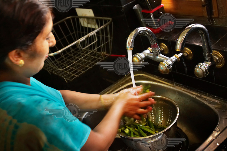 In her kitchen, a woman washes vegetables purchased at a Reliance Fresh store. Reliance Fresh is the largest in a new wave of western-style supermarkets that have recently opened across India.
