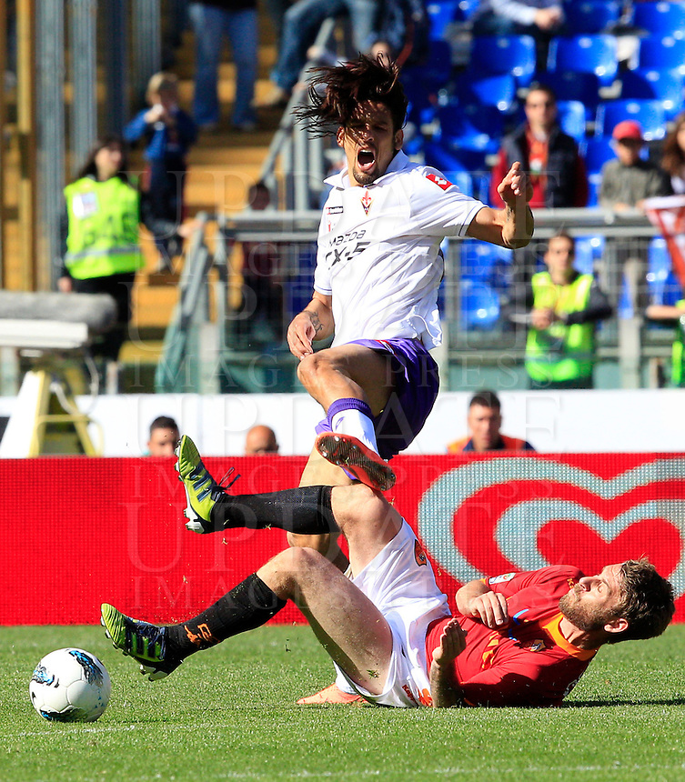 Calcio, Serie A: Roma-Fiorentina. Roma, stadio Olimpico, 25 aprile 2012. Il centrocampista della Roma Daniele De Rossi, in basso, interviene in tackle sull'attaccante della Fiorentina Amauri..AS Roma midfielder Daniele De Rossi, bottom, tackles Fiorentina forward Amauri during the Italian Serie A football match between AS Roma and Fiorentina, at Rome Olympic stadium, 25 april 2012..UPDATE IMAGES PRESS/Riccardo De Luca