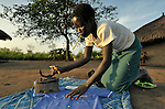 Twelve-year old Charty Moriba, a United Methodist in Pisak, a village in Southern Sudan, irons her school uniform in preparation for another day of learning.