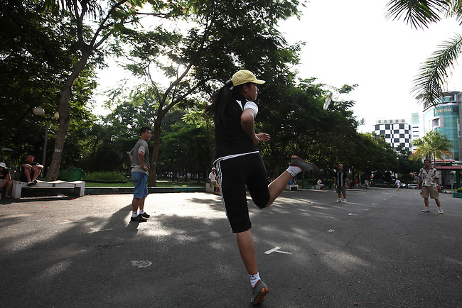 A woman returns a kick to her opponent in game similar to hackey sack at the 23/9 park in Ho Chi Minh City, Vietnam. July 5, 2011.
