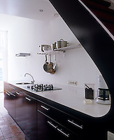 A striking black and white kitchen has been seamlessly integrated under the stunning curve of a this bespoke staircase