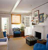 A small and comfortable sitting room has walls lined with paper and furniture grouped around a simple firepalce