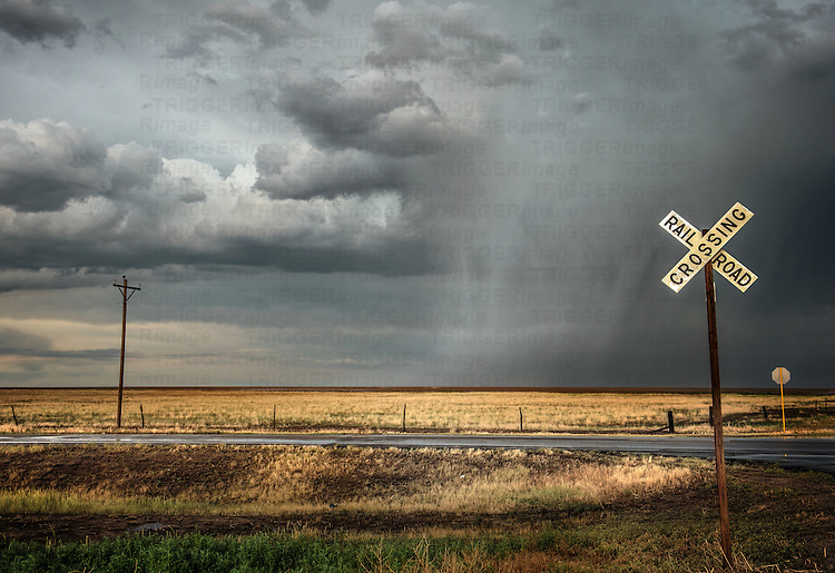 Country scene in USA with road and storm clouds and railroad crossing sign