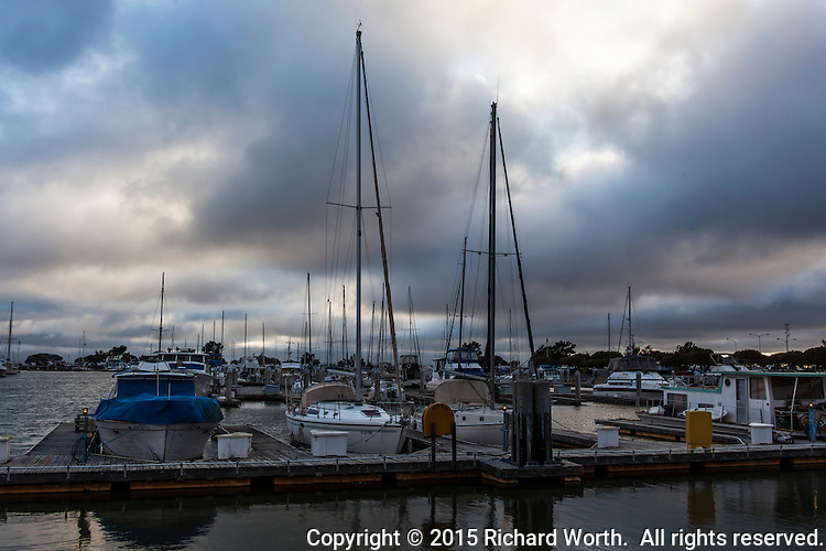 Clouds, big and dark and surrounded by wind, visit San Leandro Marina, where sail boat masts stand tall and wait.