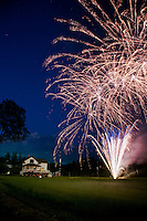 Fourth of July Indepenence Day fireworks over a farmhouse.