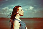 Young woman outdoors with the wind in her hair with thoughtful expression