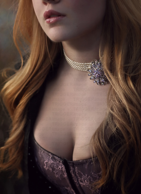 A mysterious and sensual cropped photo of a beautiful young woman's partial face with pouty lips and cleavage