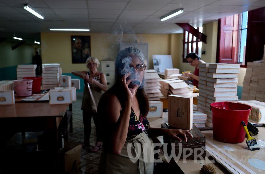 A woman smokes a cigar at the H. Upmann cigar factory in Havana, Cuba, March 01, 2017. Tourists from around the world visit to Cuba during the annual festival of the cigar, celebrate from February 27 to 3 of March.  VIEWpress/Eliana Aponte.