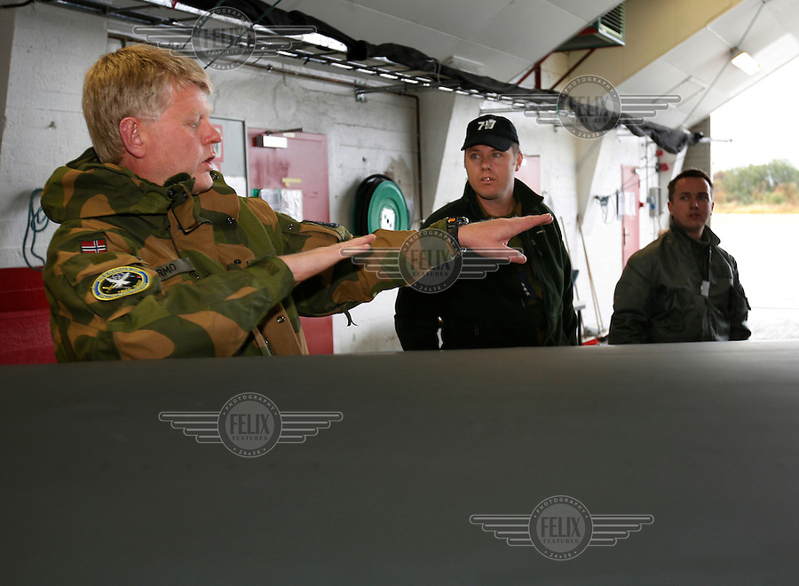 Squadron leader Hans Petter Narmo talks to colleagues  of 717 squadron about an incident. 717 squadron operates DA-20 Jet Falcon. Royal Norwegian Air Force. BOLD AVENGER 2007 (BAR 07), a NATO  air exercise at &Oslash;rland Main Air Station, Norway. BAR 07 involved air forces from 13 NATO member nations: Belgium, Canada, the Czech Republic, France, Germany, Greece, Norway, Poland, Romania, Spain, Turkey, the United Kingdom and the United States of America. The exercise was designed to provide training for units in tactical air operations, involving over 100 aircraft, including combat, tanker and airborne early warning aircraft and about 1,450 personnel.