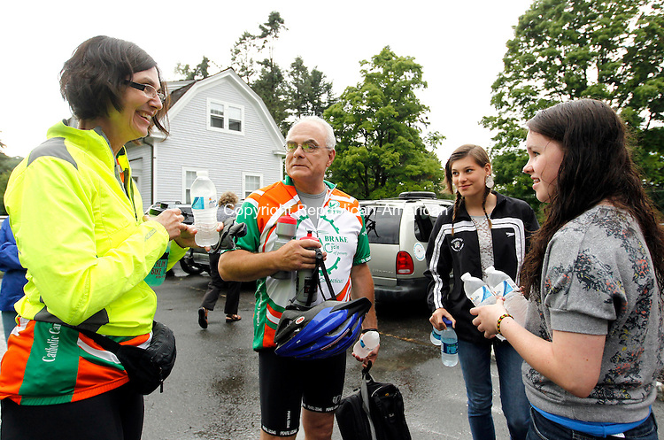 """Middlebury, CT-25 June 2012-062512CM03-  Claire Dalidowitz (left) of Kensington and Tom Sacerdote, of Rocky Hill are welcomed by Aisling Connolly (right), 15 and Francesca Holland, 14 both of Middlebury at the St. John of the Cross Parish house Monday afternoon in Middlebury.  The """"Brake the Cycle"""" team, a group of men and women who cycle for a week each summer to raise awareness for poverty issues, stopped by the parish house during the journey.  Father Dennis Vincenzo opened up the house for the team to stay.     Christopher Massa Republican-American"""