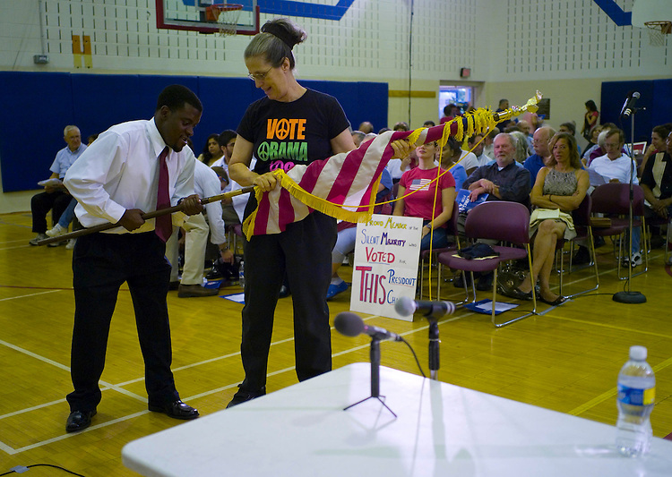 GERMANTOWN, MD - August 25: Edwards staffer Rahsheim Wright gets a hand from audience memeber Mary Ellis, of Carroll County, Md., setting up a U.S. flag before a town hall meeting in Germantown, Md., hosted by Rep. Donna Edwards, D-Md., on healthcare legislation before the U.S. Congress. (Photo by Scott J. Ferrell/Congressional Quarterly)