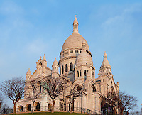PARIS, FRANCE - JANUARY 20: A low angle view of  Sacré-Coeur Basilica, on January 20, 2009, in Montmartre, Paris, France. Sacré-Coeur Basilica, built 1884-1914, was designed by Paul Abadie. Constructed in white travertine on the top of the Butte Montmartre, the Romano-Byzantine style Sacré-Coeur was designed as a monument to those who died in the Paris Commune during the Franco-Prussian War, 1870-71.  Its clustered white domes are seen against a clear sky on a winter morning. (Photo by Manuel Cohen)