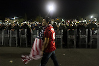 A USA fan celebrates while being escorted by Mexican police officers in riot gear after the USA tied Mexico at their World Cup Qualifier at Azteca stadium in Mexico City, Mexico on March 26, 2013.