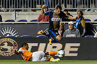 Daniel Cruz (44) of the Philadelphia Union jumps over the tackle of Ricardo Clark (13) of the Houston Dynamo. The Houston Dynamo defeated the Philadelphia Union 1-0 during a Major League Soccer (MLS) match at PPL Park in Chester, PA, on September 14, 2013.