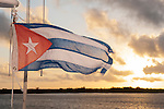 Gardens of the Queen, Cuba; a Cuban flag flutters in the wind, while in the background the sun rises over a tropical island in the Gardens of the Queen